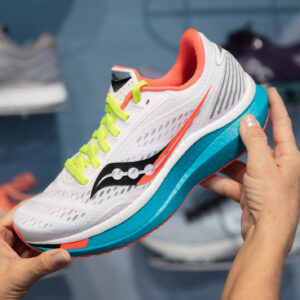 woman showing off a running shoe with bright colors