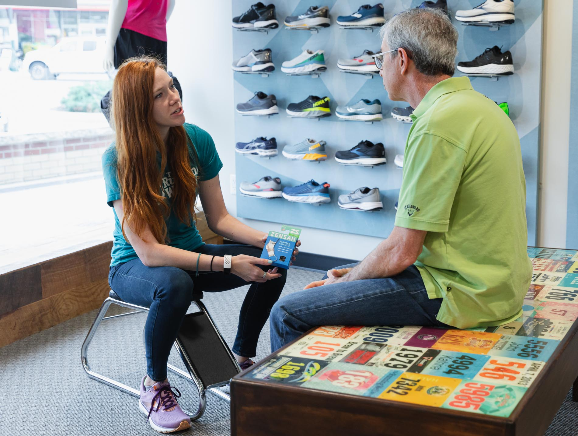 man discussing running socks with a running well store employee to assist with plantar fasciitis pain