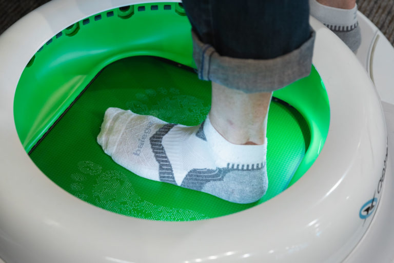 man measuring his feet using state-of-the-art technology at the running well store in kansas city