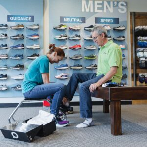 woman tying laces for man trying on running shoes in kansas city