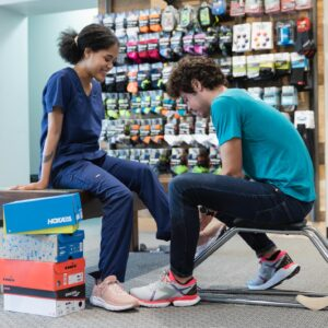 running well employee helping nurse try on shoes for standing and walking