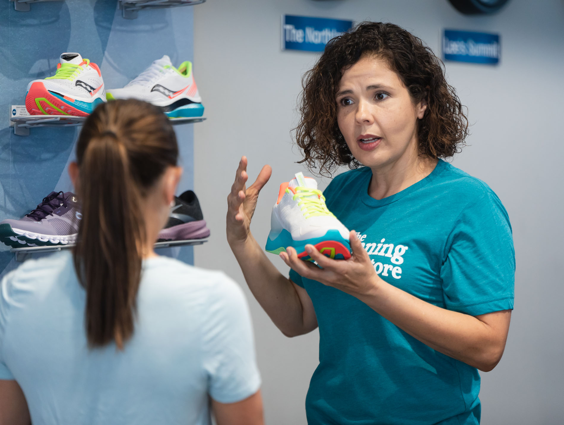 the running well store employee explaining proper shoe fit to a customer