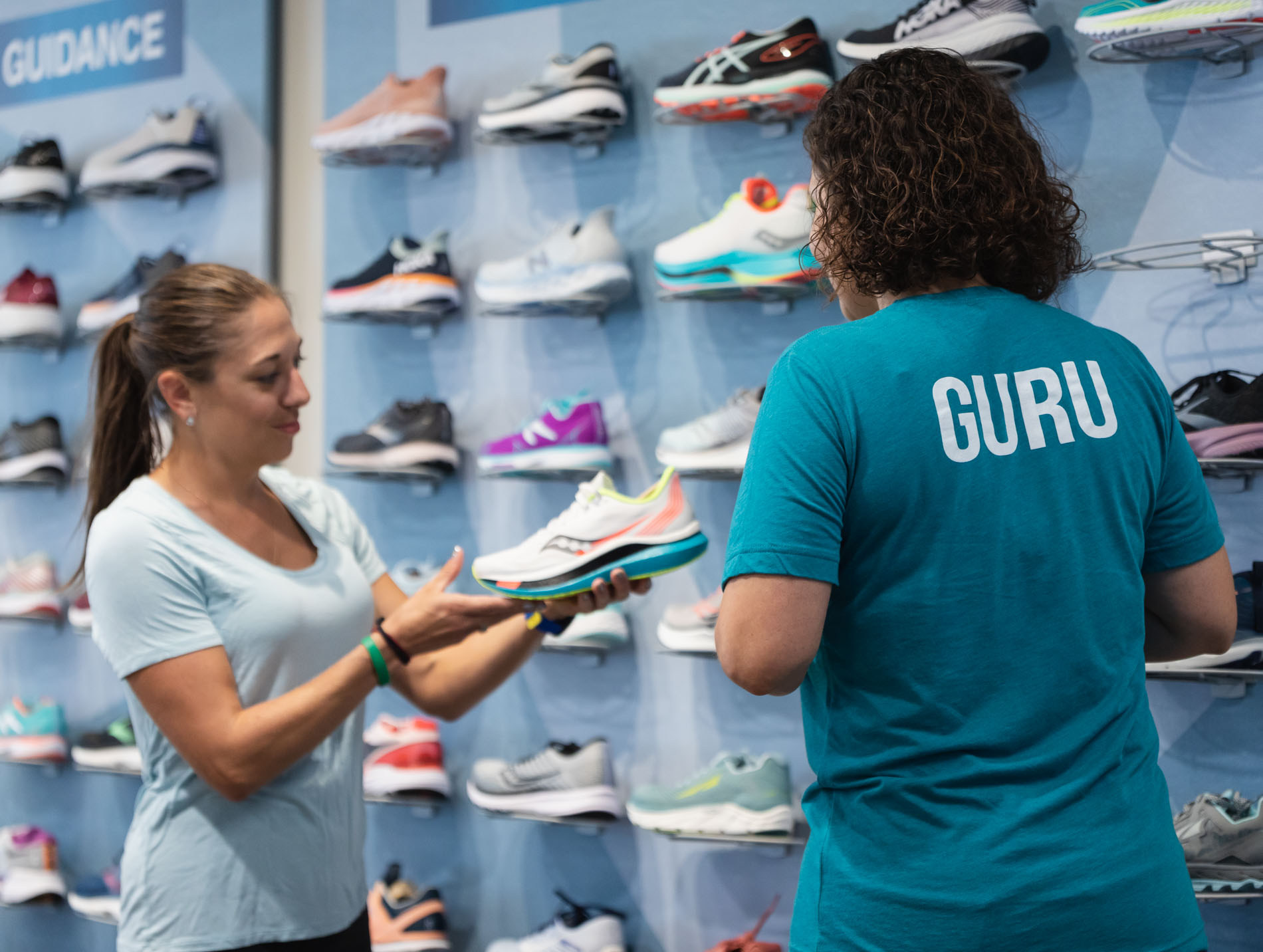 woman picking out a running shoe in kansas city