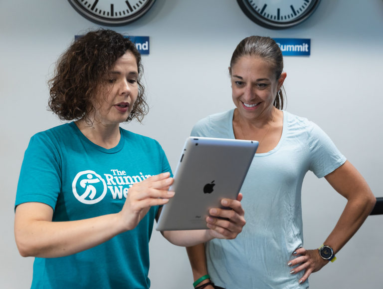 two women reading ipad to discover proper stride analysis and running shoe fit