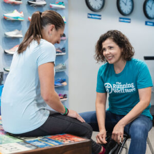 customer trying on running shoes with the help of a running well store employee