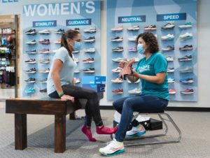 running well employee showing a customer how to assess the tread of a running shoe