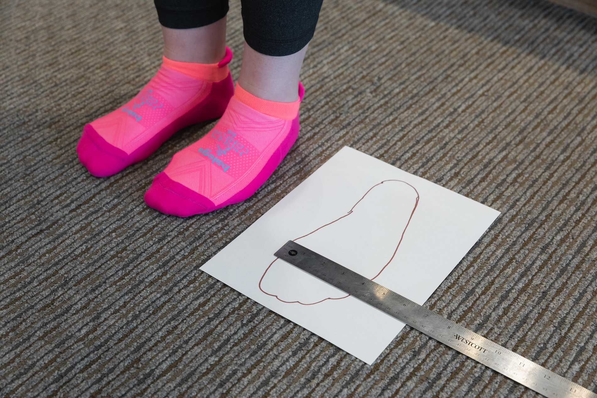 a stride analysis at the running well store, showing the tracing and horizontal measurement of the foot