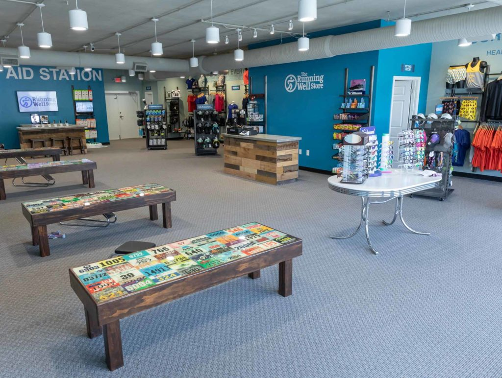 image of the running well store interior - featuring workout clothes, sunglasses, and more
