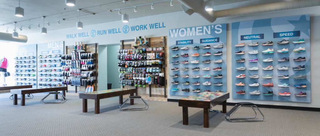 image of the running well store, including try-on areas and a wall of running shoes, socks, and more running products available in kansas city