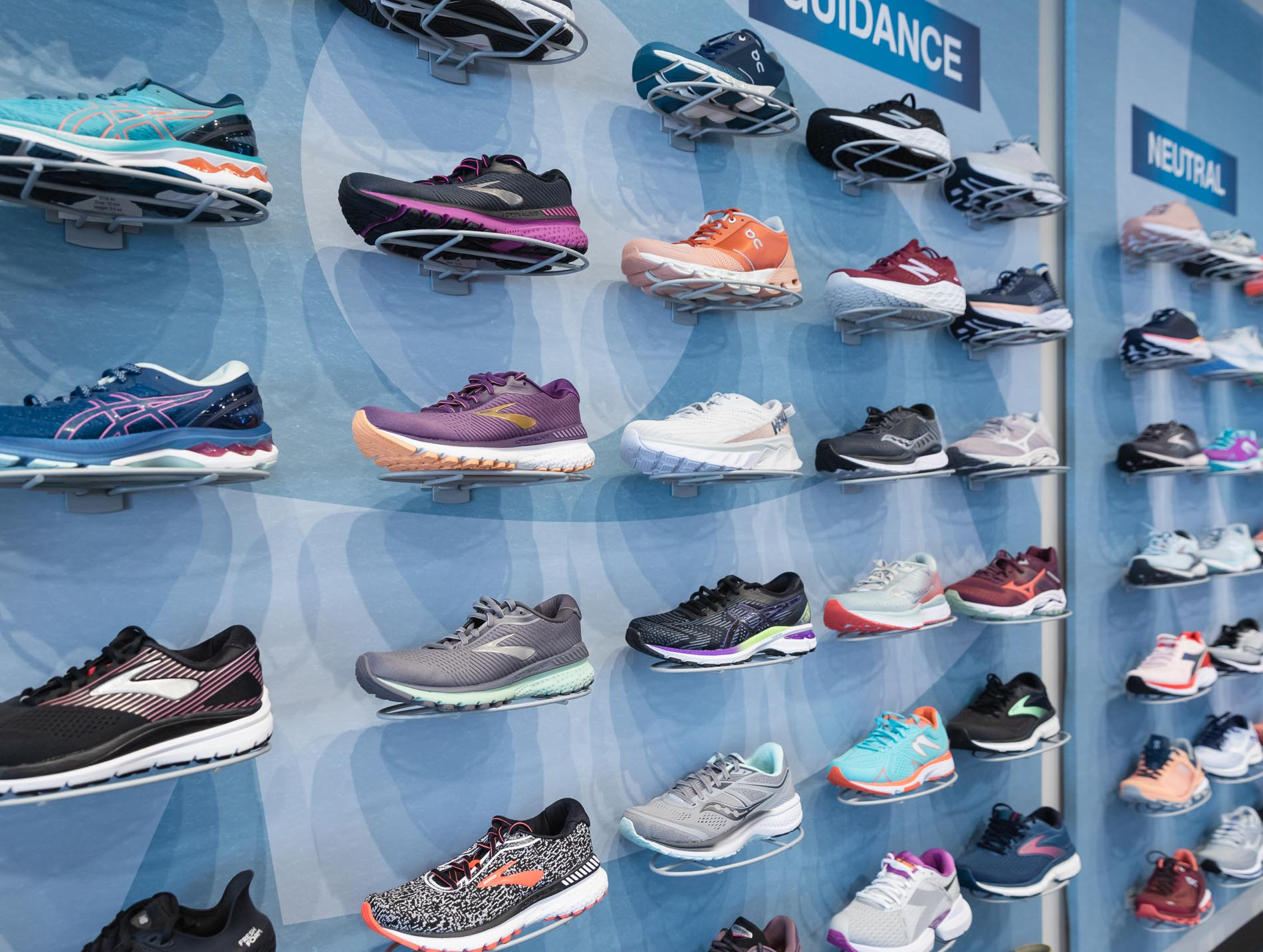 wall of running shoes available at the running well store in kansas city
