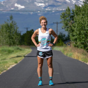 woman smiling and modeling a floyd's recovery product tee on a running trail