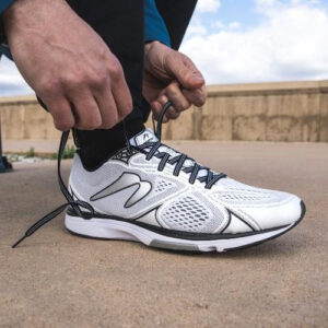 man bending over to tie shoelaces of running shoes