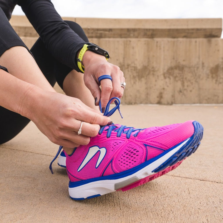 woman sitting on ground tying shoelaces of running shoes