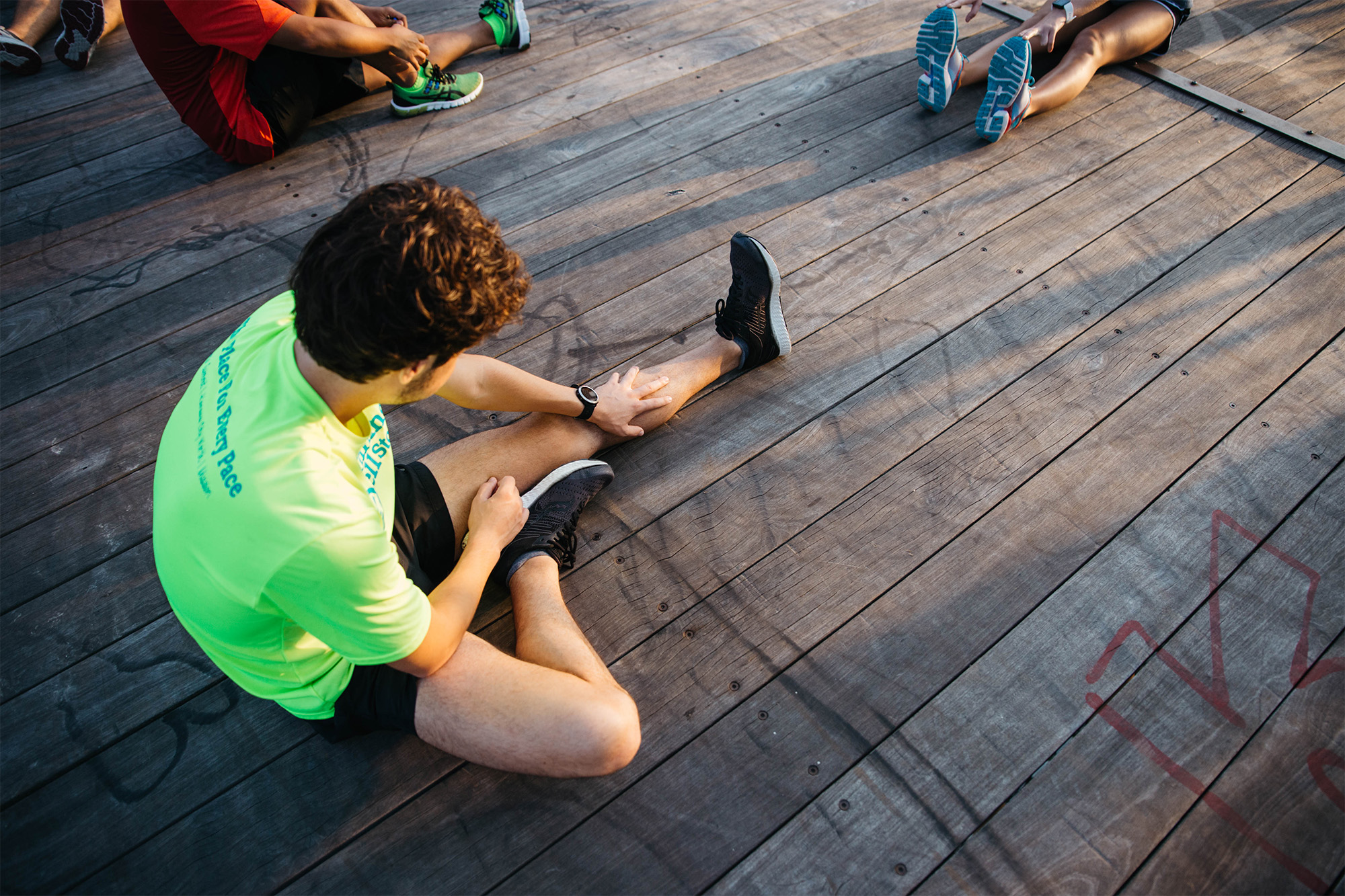 person stretching for extra flexibility and to protect their knees before a group run