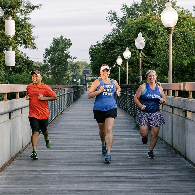 three people running on a bridge in kansas city wearing gear from the running well store