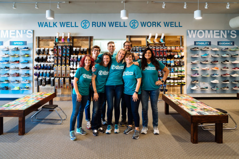group of fit gurus at the running well store wearing gear and standing in front of running socks and running shoes