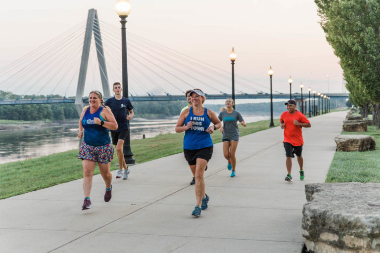 group of friends running at dusk along the river in north kansas city