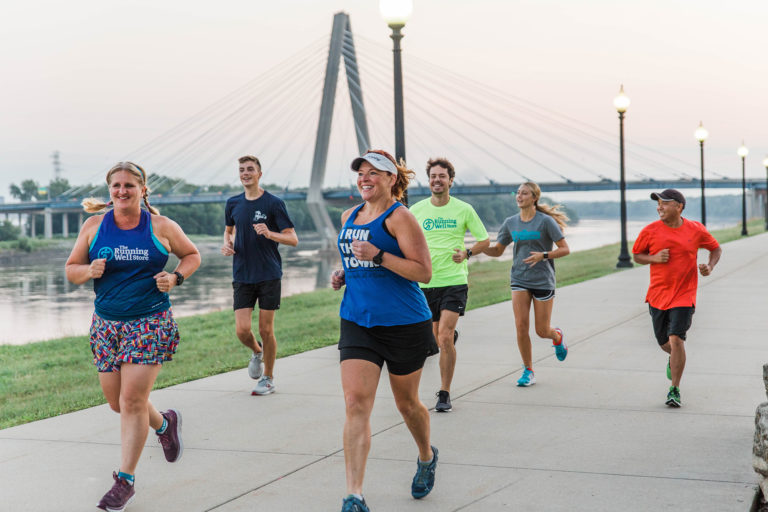 group of runners on a concrete path along the river in kansas city