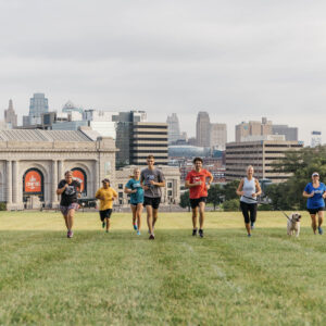 diverse group of runners in front of the kansas city skyline