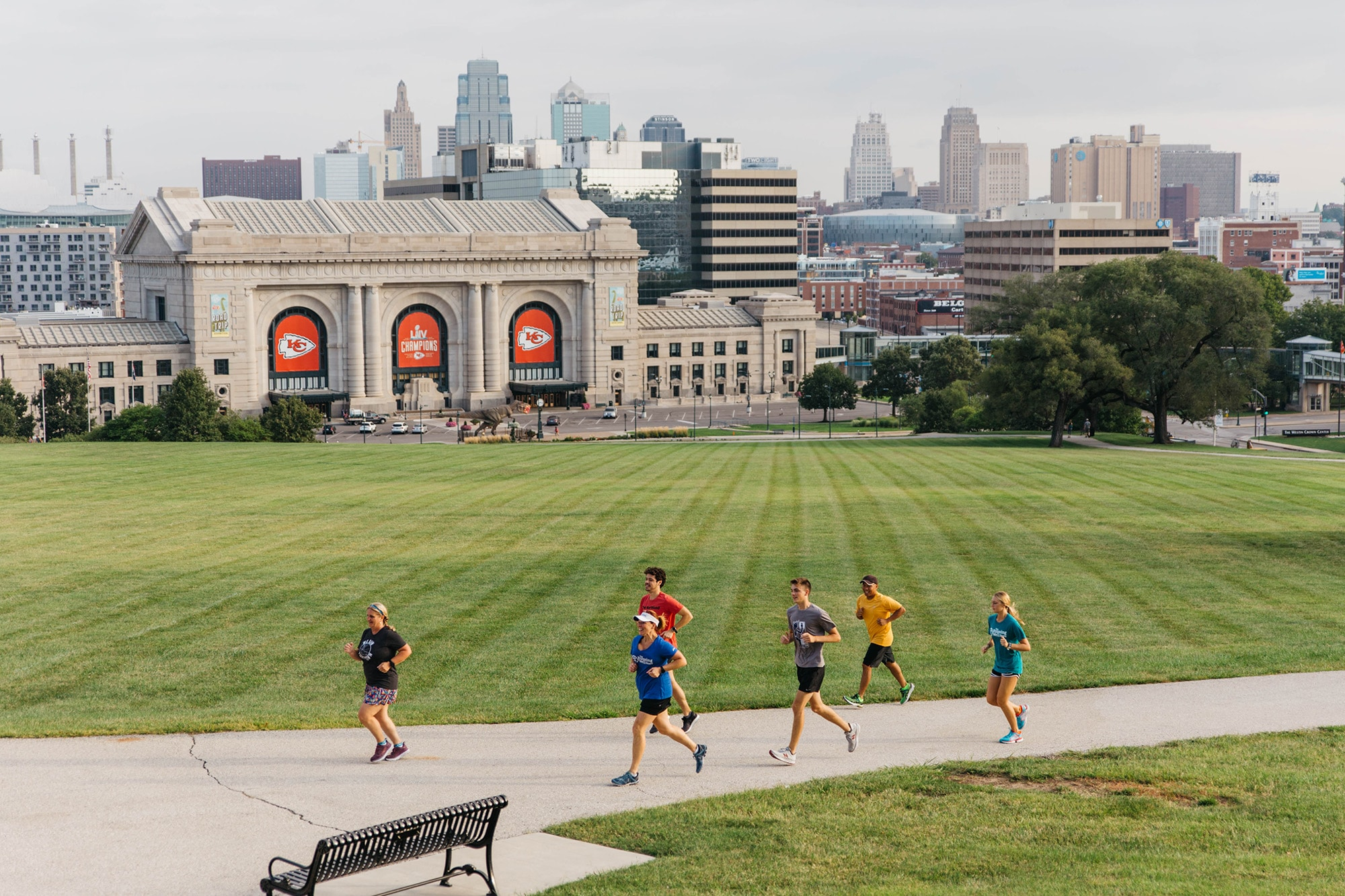 group of runners jogging in front of union station building with kansas city skyline in background