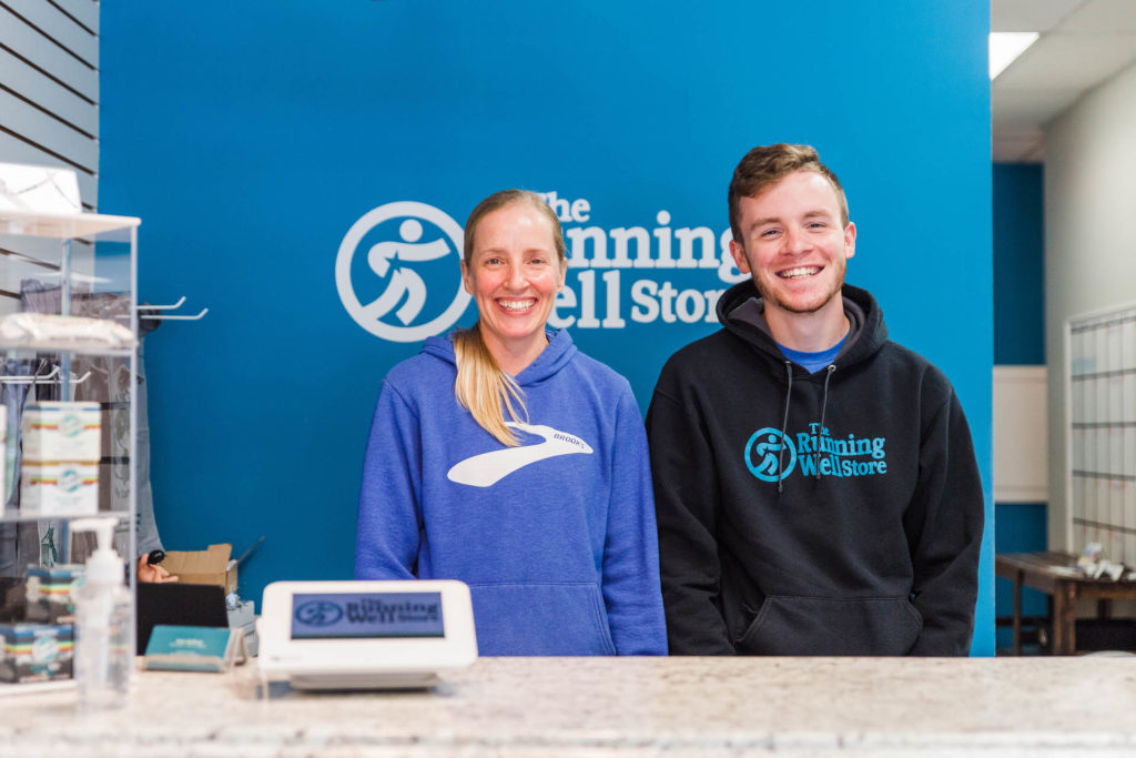 running well store employees smiling behind a counter - helping client find running shoes