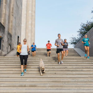 group of friends jogging at the liberty memorial in kansas city