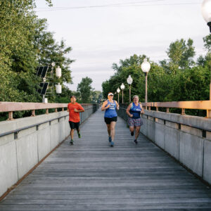 group of friends running on a bridge with brand new running shoes in kansas city