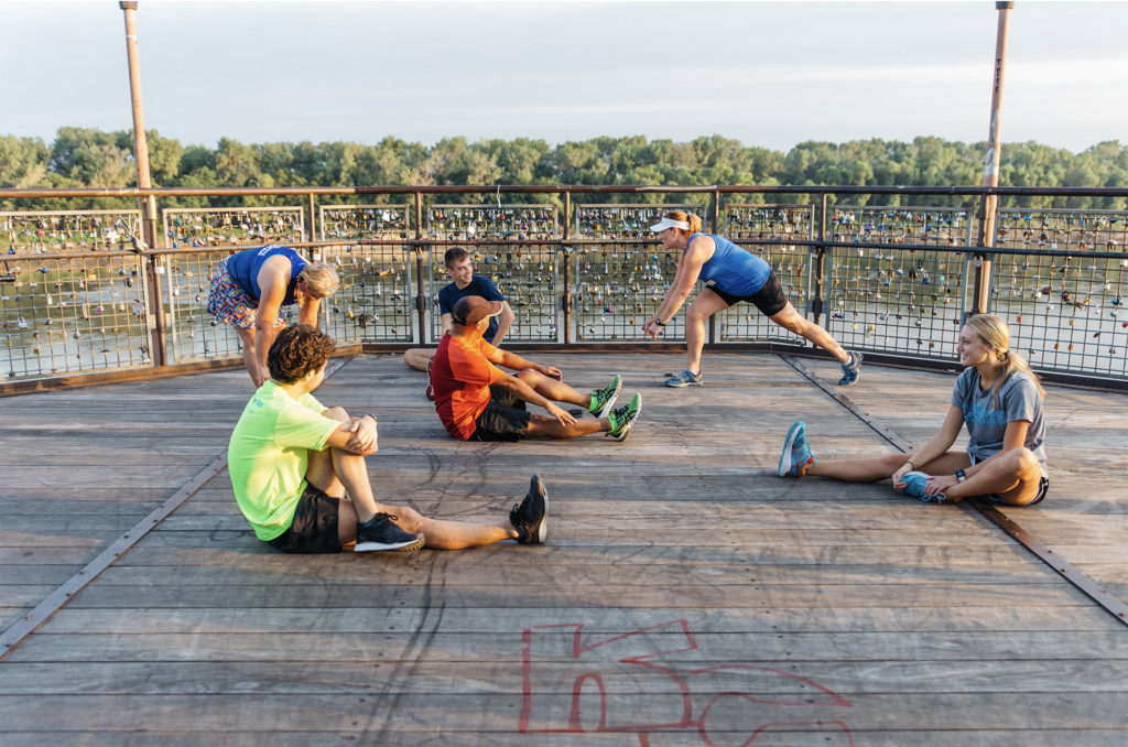 group of friends stretching before a run and discussing their running shoes in the river market of kansas city