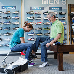 TRWs Fit Guru Mary Nacrelli fitting a client for walking shoes